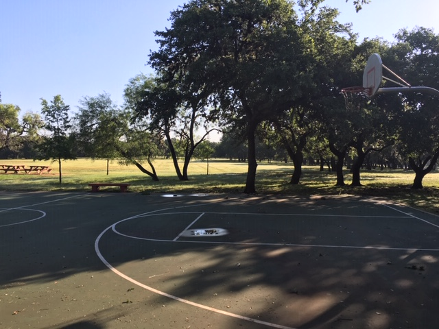 An outdoor basketball court at Blossom Park in San Antonio, which was well shaded in the morning.