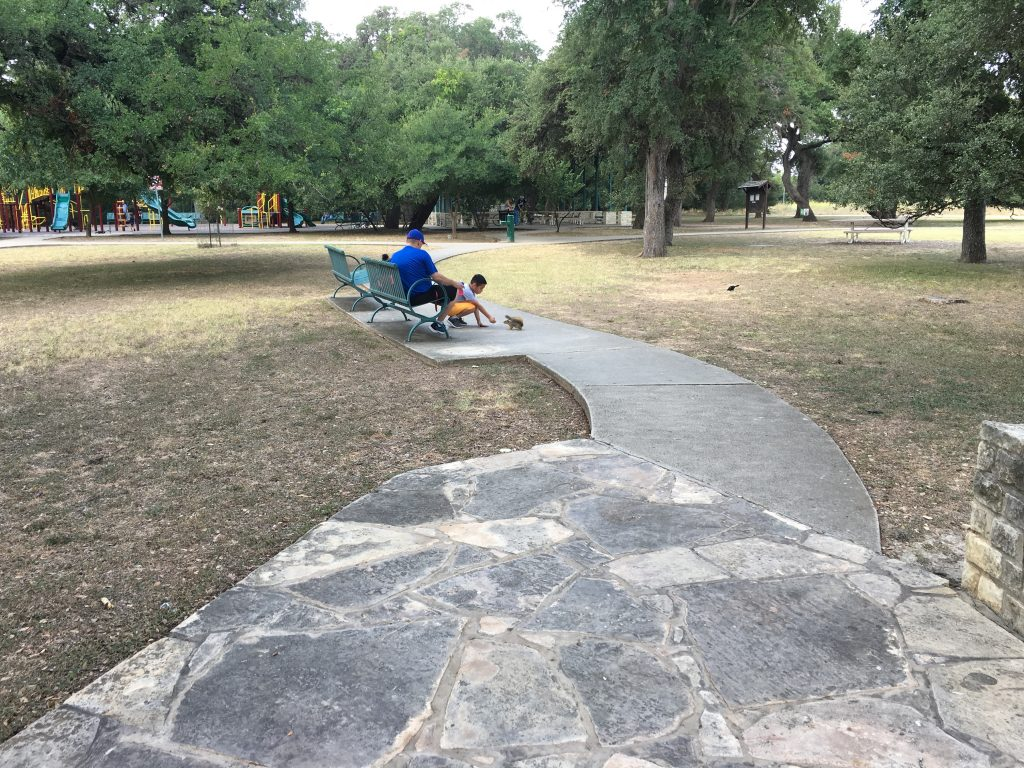 A young boy feeds a squirrel by hand at Walker Ranch Historic Park in San Antonio.