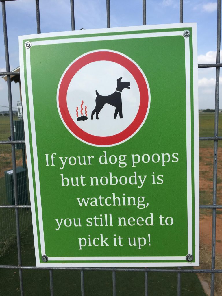 A sign encouraging people to pick up poop at a dog park.