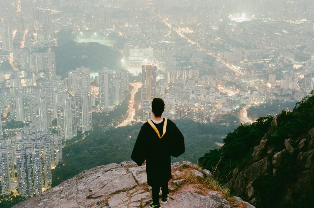 A graduate stands on top of the world after completing his education.