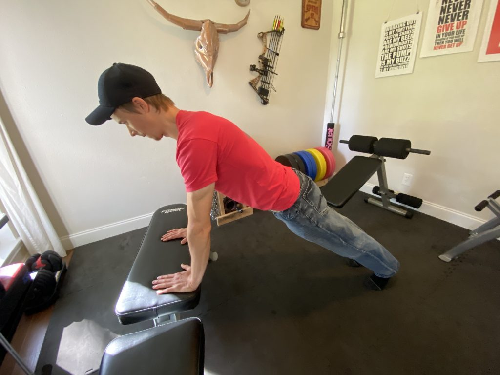 The starting position of the low inclined push-up on a weight bench is another great way to do push-ups for beginners.